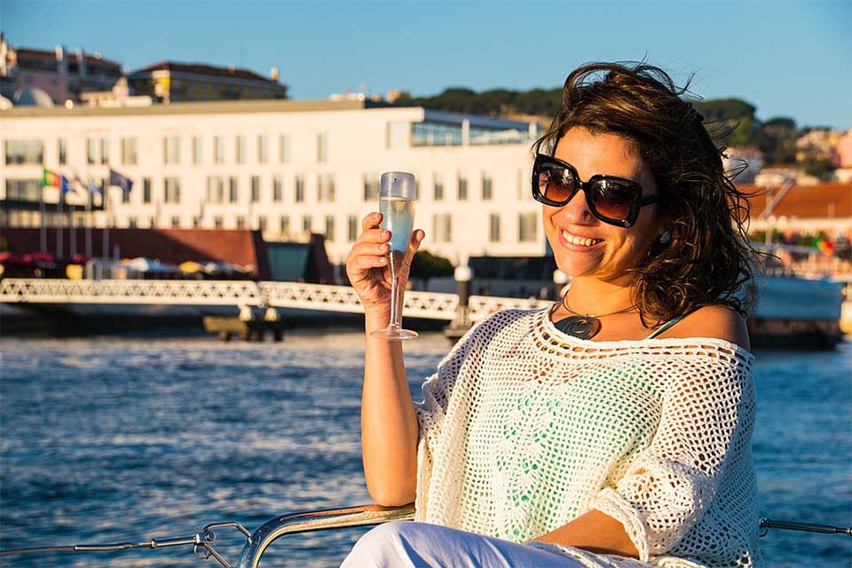 A woman drinking champagne in a boat on the River Tagus, Lisbon